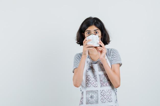 Маленькая девочка в футболке, фартук держит модель дома и выглядит озадаченно,