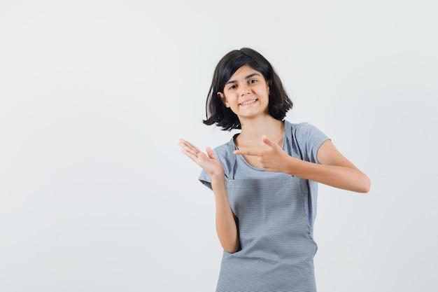 Маленькая девочка в футболке, фартук, указывающий на что-то, притворившийся удерживаемым, и уверенный вид, вид спереди.