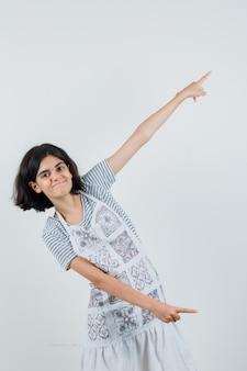T- 셔츠에있는 어린 소녀, 위아래를 가리키는 앞치마와 쾌활한 찾고,