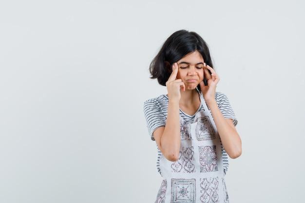 티셔츠를 입은 어린 소녀, 앞치마가 두통으로 고통 받고 피곤해 보입니다.