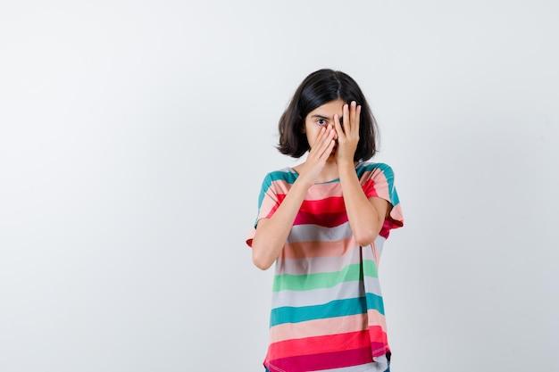 티셔츠를 입은 어린 소녀가 손으로 얼굴을 덮고 손가락을 통해 바라보고 진지한 정면을 바라보고 있습니다.