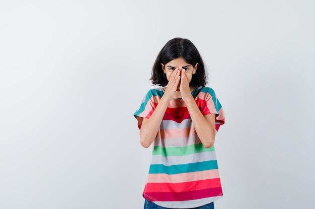 티셔츠를 입은 어린 소녀가 손으로 코와 입을 가리고 흥분한 표정을 짓고 있습니다.