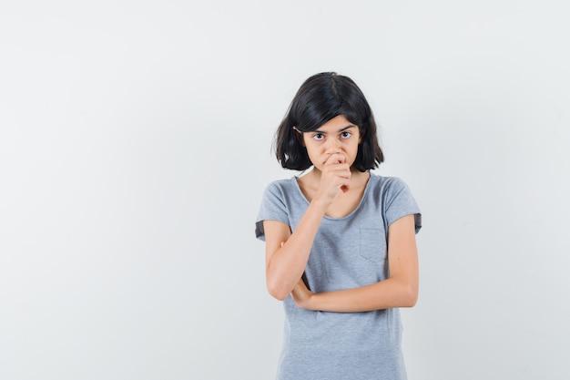あごに手をつないで躊躇しているtシャツの少女、正面図。
