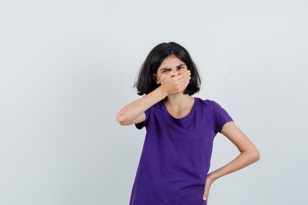 Маленькая девочка в футболке, взявшись за рот и выглядя обеспокоенной,