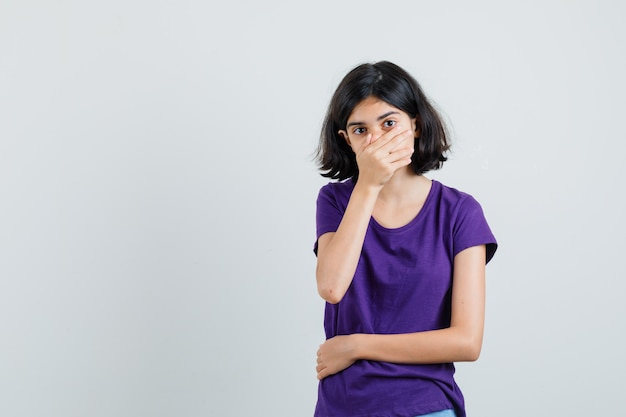 Маленькая девочка в футболке, взявшись за рот и удивившись,