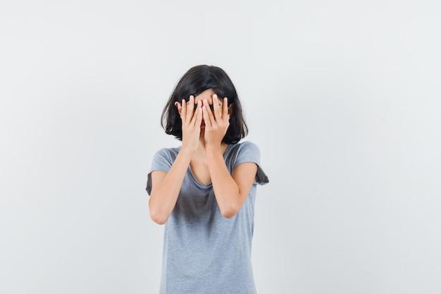 Маленькая девочка в футболке, взявшись за руки на лице и выглядя испуганной, вид спереди.