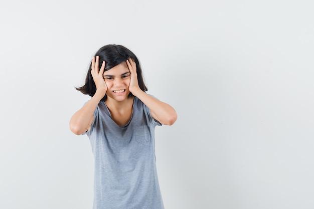 Маленькая девочка в футболке, взявшись за руки на голове и глядя с сожалением, вид спереди.
