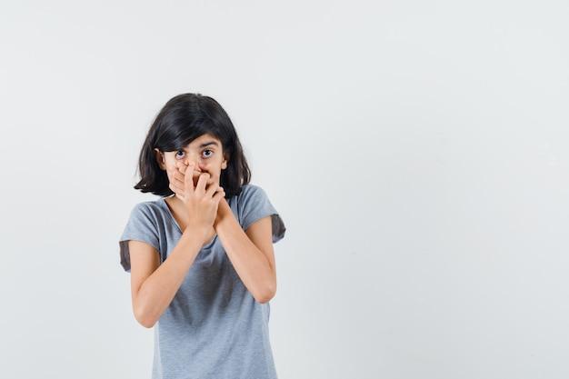 Маленькая девочка в футболке, взявшись за руки рот и выглядя испуганной, вид спереди.