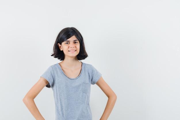 Маленькая девочка в футболке, взявшись за руки на талии и выглядя уверенно, вид спереди.