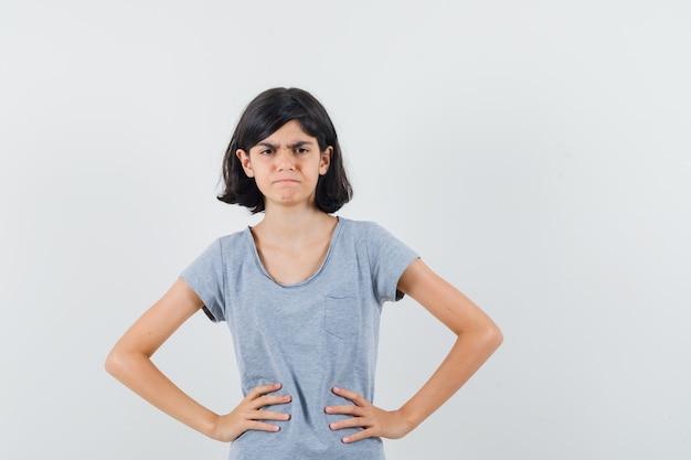 腰に手をつないで、ダウンキャスト、正面図を見てtシャツを着た少女。