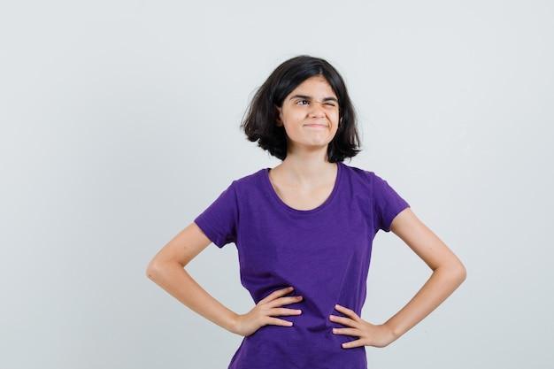 腰に手をつないで楽観的に見えるtシャツの少女、