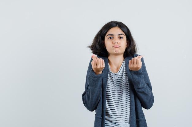 Маленькая девочка в футболке, куртке делает денежный жест и выглядит бедной,