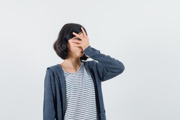 Tシャツを着た少女、顔に手をつないで忘れっぽいジャケット