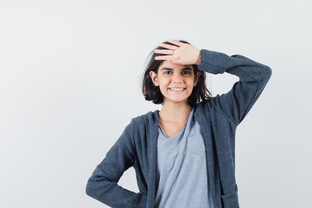 T- 셔츠, 이마에 손을 잡고 명랑 한, 전면보기 재킷에 어린 소녀.