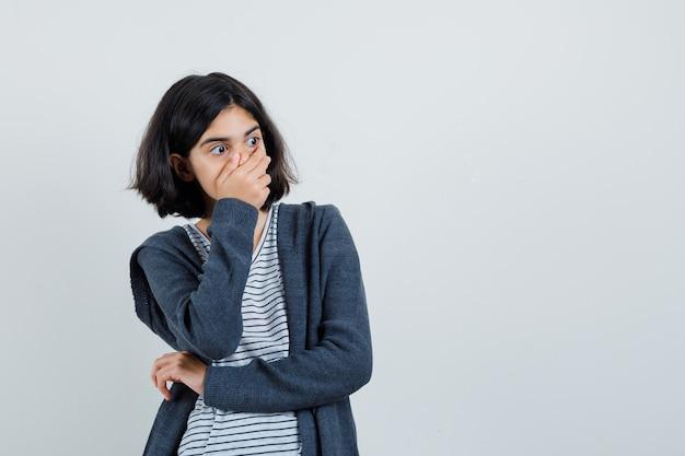 Tシャツを着た少女、口に手をつないで驚いて見えるジャケット、