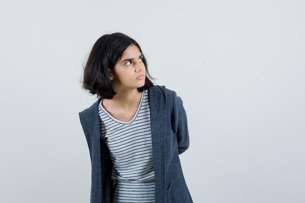 Tシャツを着た少女、後ろで手を握り、集中して見えるジャケット