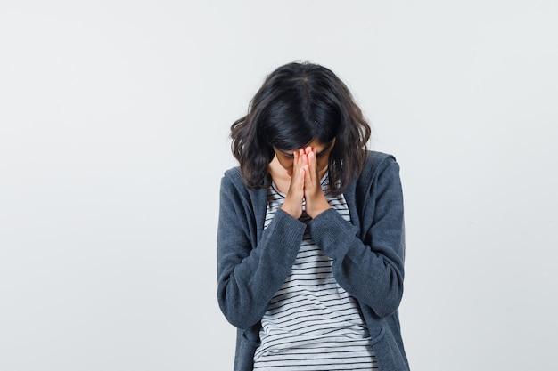 Маленькая девочка в футболке, куртке, взявшись за руки в молящемся жесте и выглядящей с надеждой