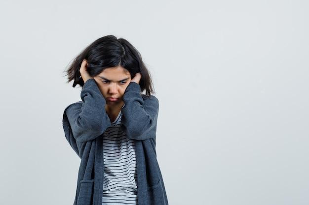 T- 셔츠에있는 어린 소녀, 재킷 귀에 손을 잡고 고뇌보고,