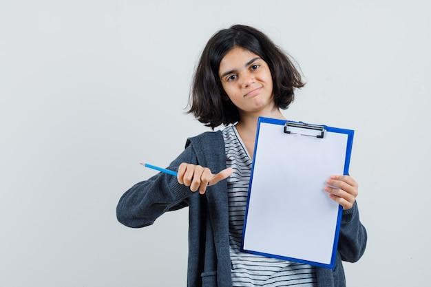 T- 셔츠에있는 어린 소녀, 클립 보드를 가리키는 재킷, 연필을 들고 자신감을 찾고,