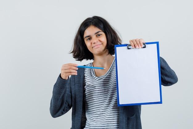 T- 셔츠에있는 어린 소녀, 연필로 클립 보드를 가리키고 자신감을 찾고 재킷,