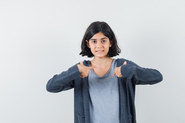 Маленькая девочка в футболке, пиджаке смотрит на себя в вопросительном жесте и выглядит оптимистично
