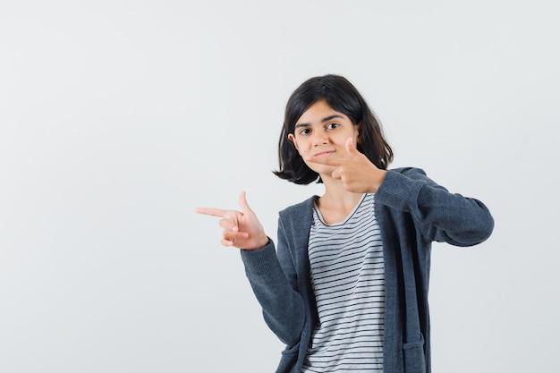 Tシャツを着た少女、左側を指して自信を持って見えるジャケット
