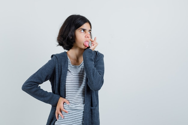 Маленькая девочка в футболке, пиджак, отрывая веко, высунув язык,
