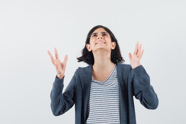 Tシャツを着た少女、見上げて感謝しながら手を上げるジャケット