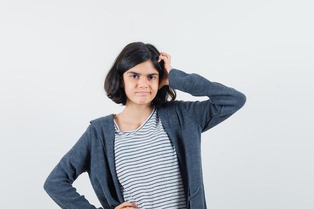 Tシャツ、ジャケットの頭を引っ掻いて思慮深く見える少女