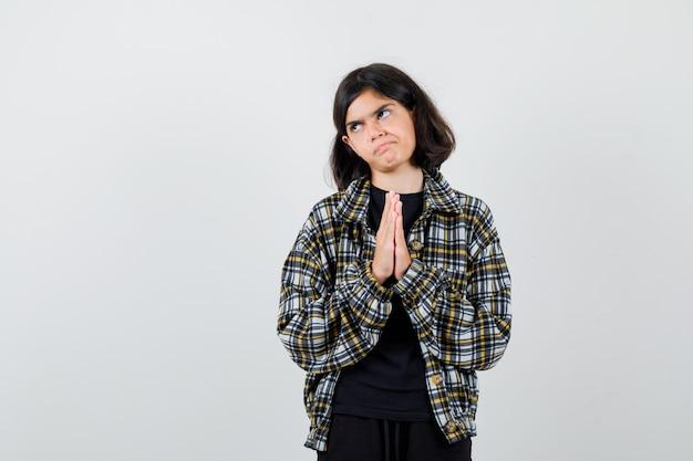 Маленькая девочка в футболке, куртка показывает сложенные руки в умоляющем жесте и смотрит с надеждой, вид спереди.