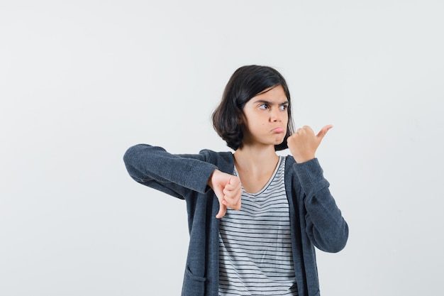 Tシャツを着た少女、親指を上下に見せて躊躇しているジャケット