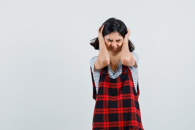 Tシャツを着た少女、手で頭を握りしめ、ストレスを感じているジャンプスーツ、