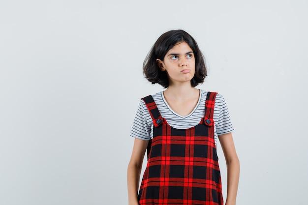 T- 셔츠에있는 어린 소녀, 뭔가에 초점을 맞추고 잠겨있는 찾고 점프 슈트,