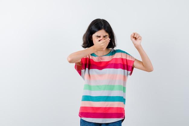 Маленькая девочка в футболке держит руку на рте, поднимает руку и выглядит с отвращением, вид спереди.