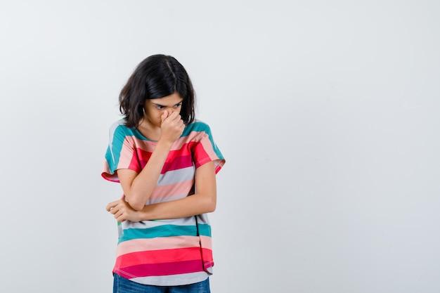 Маленькая девочка в футболке держит руку на носу и выглядит грустно, вид спереди.
