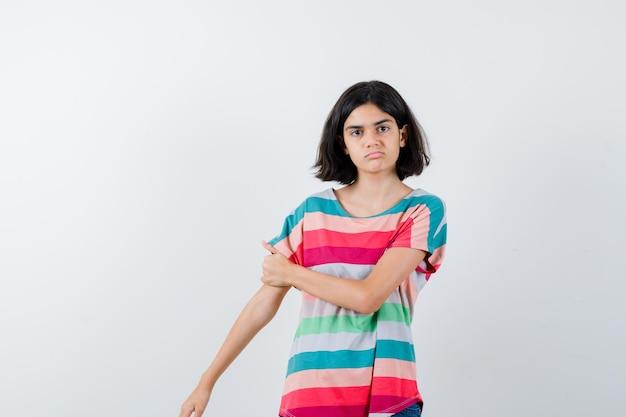 もう一方の腕に手を保ち、真剣に見えるtシャツの少女、正面図。