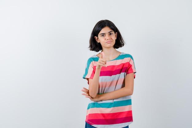티셔츠를 입은 어린 소녀가 가리키고 자신감 있고 앞모습을 보고 있습니다.