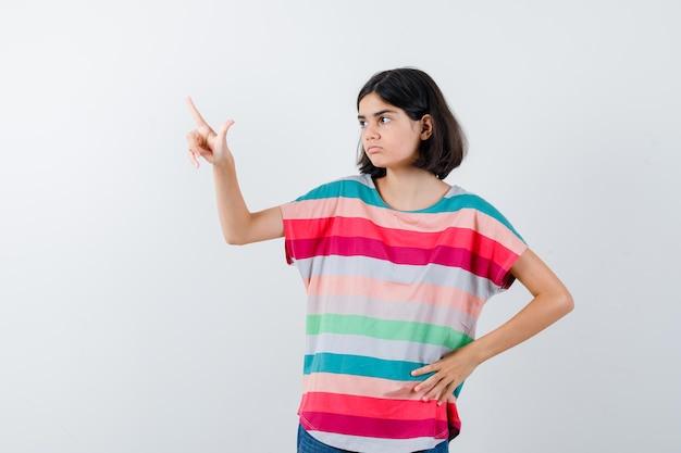 Маленькая девочка в футболке, указывая вверх и глядя сосредоточенно, вид спереди.