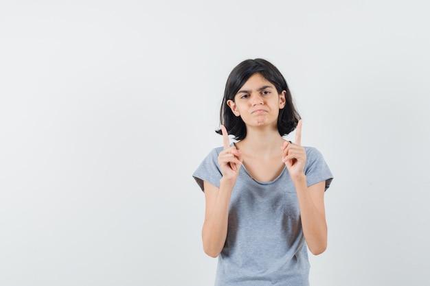 絶望的な、正面を向いて見ているtシャツの少女。