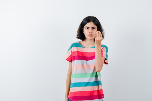Маленькая девочка в футболке показывает итальянский жест и выглядит серьезным, вид спереди.