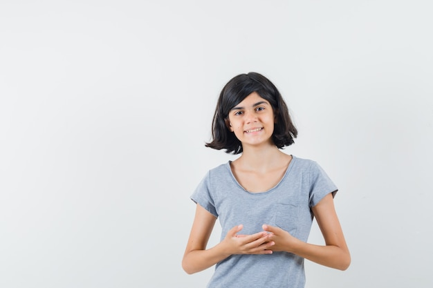 思考ポーズで立って自信を持って見えるtシャツの少女、正面図。