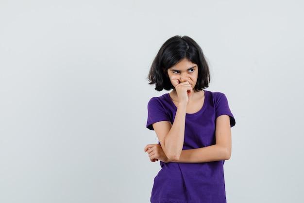 思考ポーズで立って悲しそうに見えるtシャツの少女、