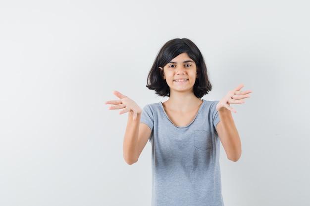 Маленькая девочка в футболке протягивает руки и выглядит веселой, вид спереди.