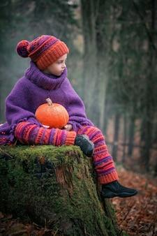 秋の森の少女は、ニットのスーツとカボチャを手に持ったアンズタケの耳を持つ帽子の苔むした木の切り株に座っています