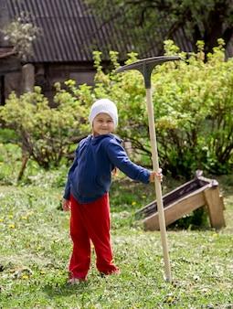 Маленькая девочка на даче с граблями