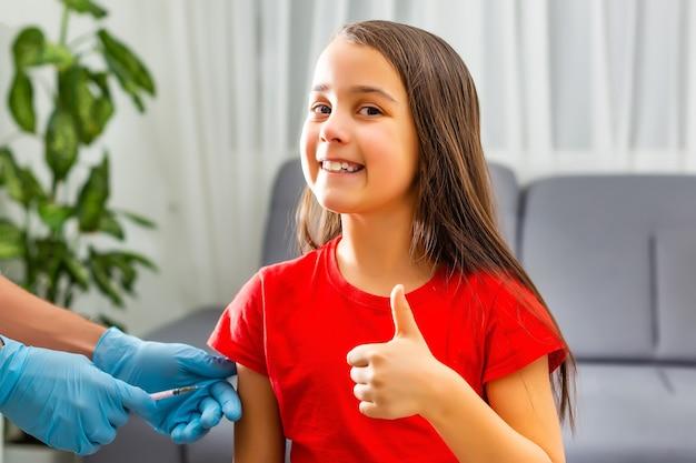 診療所の少女は予防接種を受けています。 covid-19コロナウイルス、インフルエンザ、危険な感染症に対するワクチンの注射器。人間、子供のための臨床試験後の注射。医学濃度