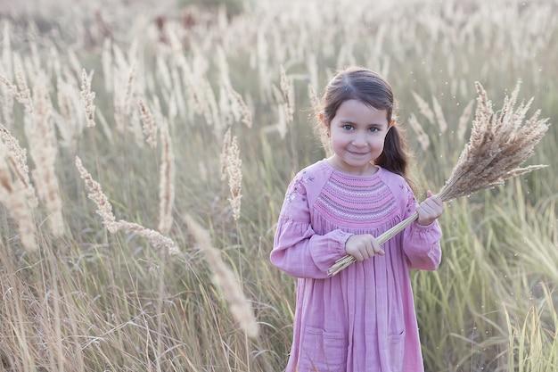 Маленькая девочка в поле держит букет пшеницы.