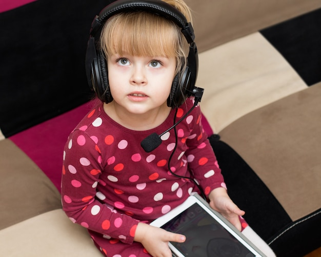 타블렛와 헤드폰에서 어린 소녀
