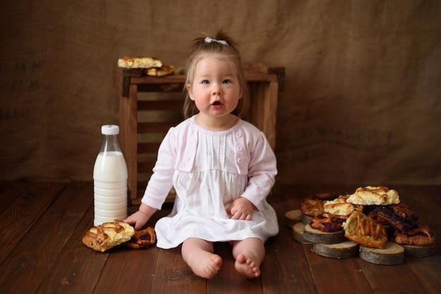 台所の少女は甘いペストリーを食べる。
