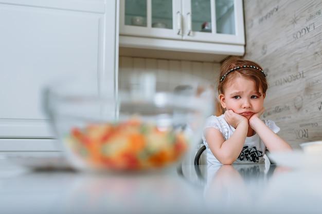 台所の小さな女の子はテーブルに座って、退屈しています